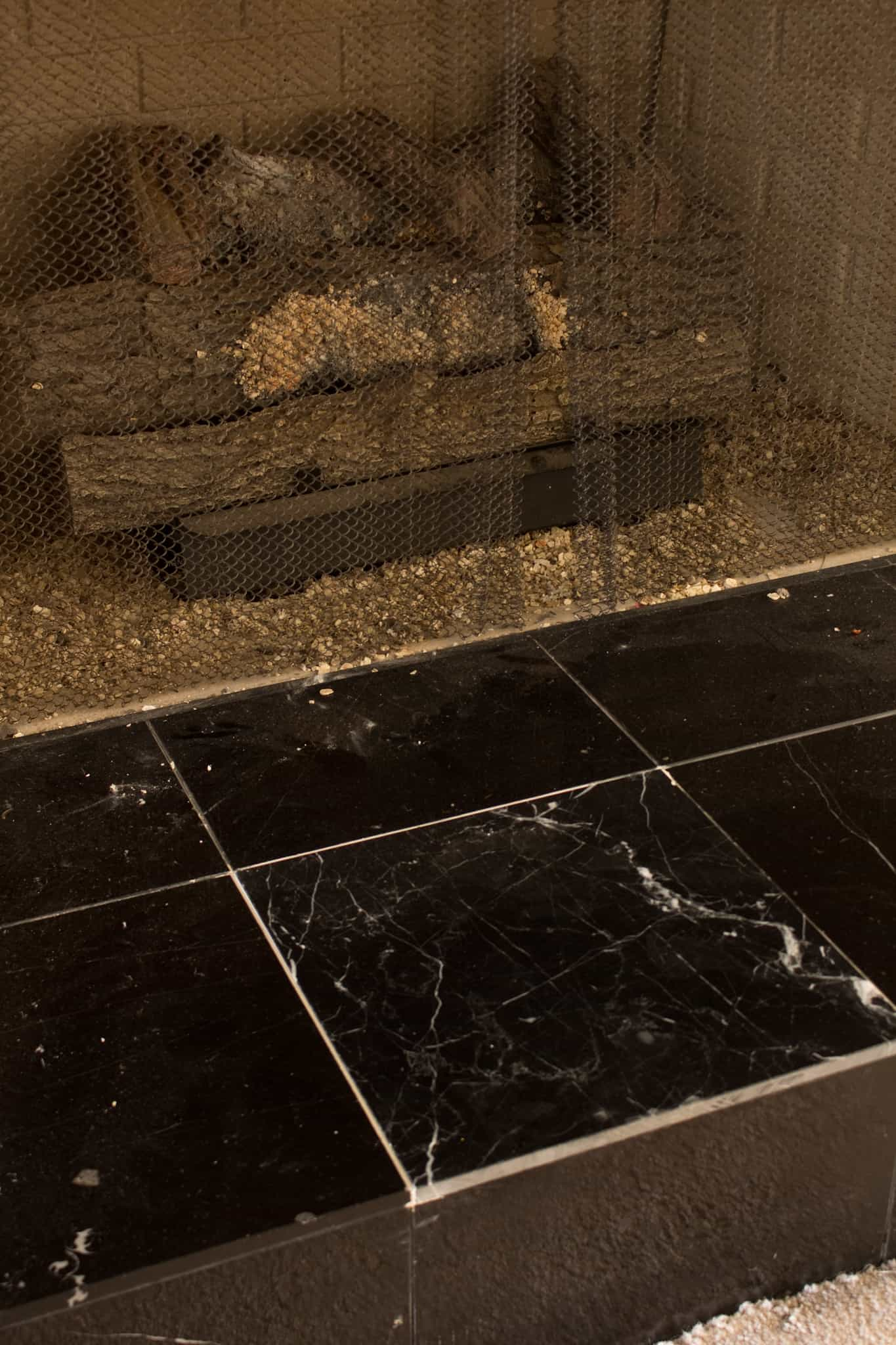 I painted our damaged, black tiles on our fireplace to look like marble. It was easy, and it looks beautiful!