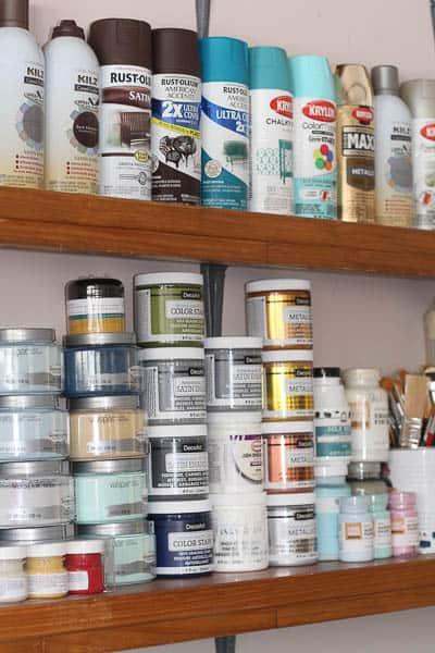 How to organize crafts when you don't have a craft room is to use a wall in your garage. You can store paint on small shelves and use crates for the rest of your supplies.