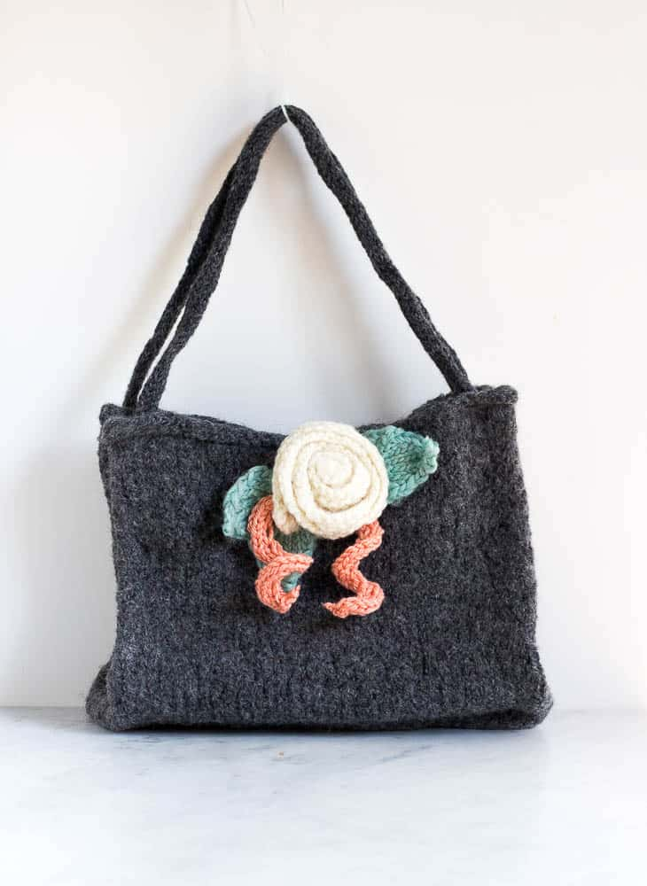 This felted knitted bag is knitted with only the knit stitch with 100% wool yarn. The knitted bag has been washed in the washing machine to felt the bag.