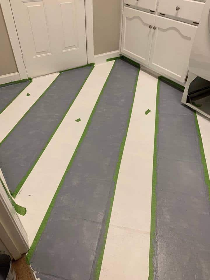 Painting stripes on the buffalo check painted floor.