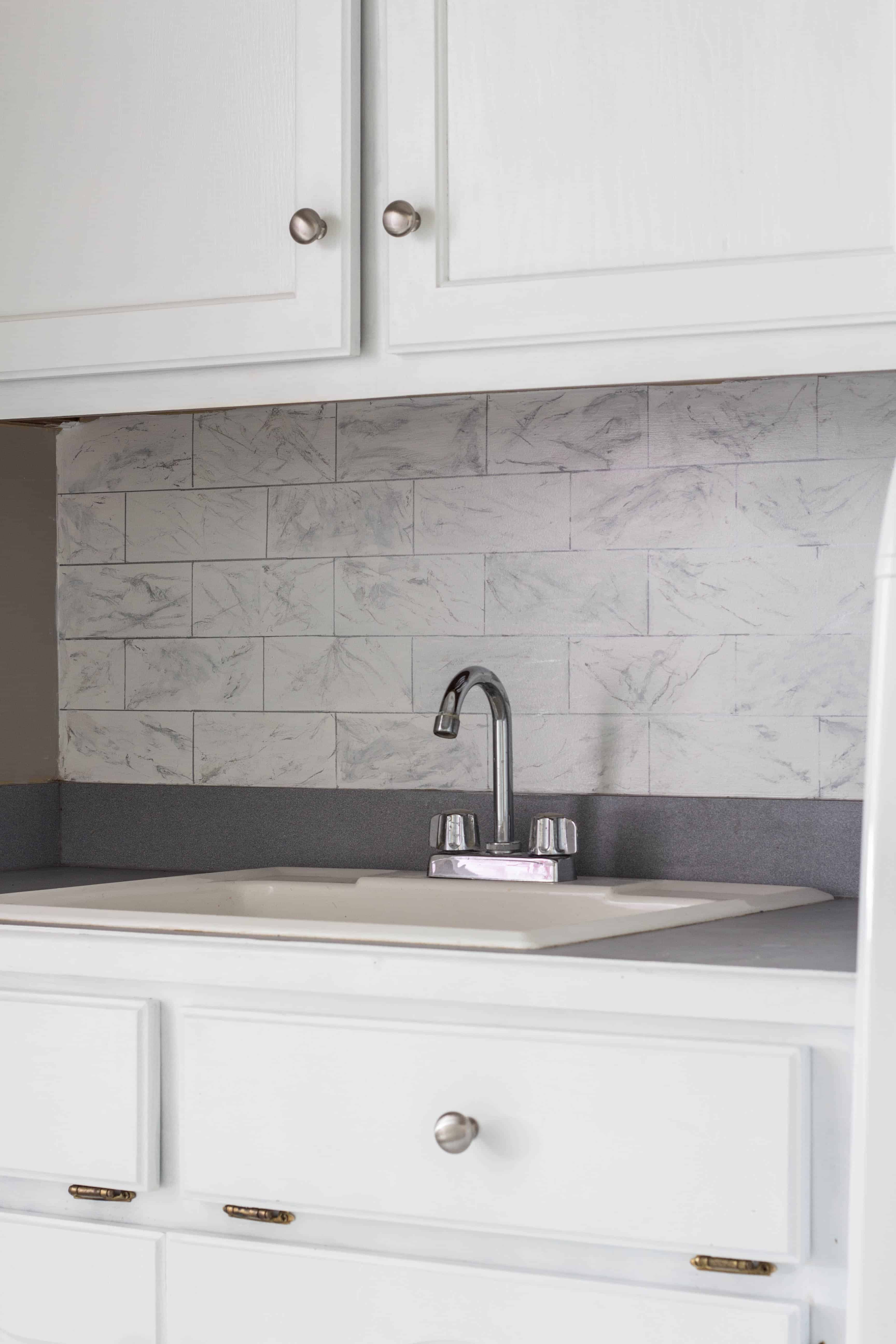 Faux marble backsplash in laundry room makeover for the $100 Room Challenge.
