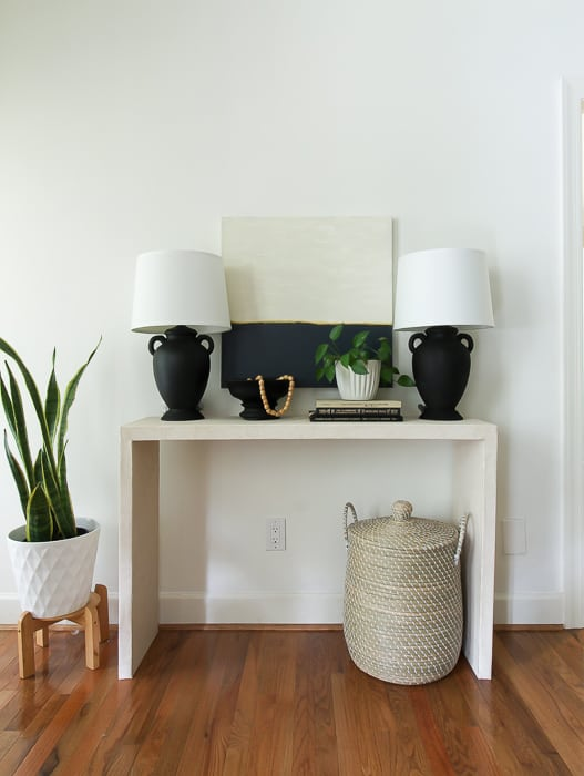 DIY faux concrete console table made with boards and wallpaper.