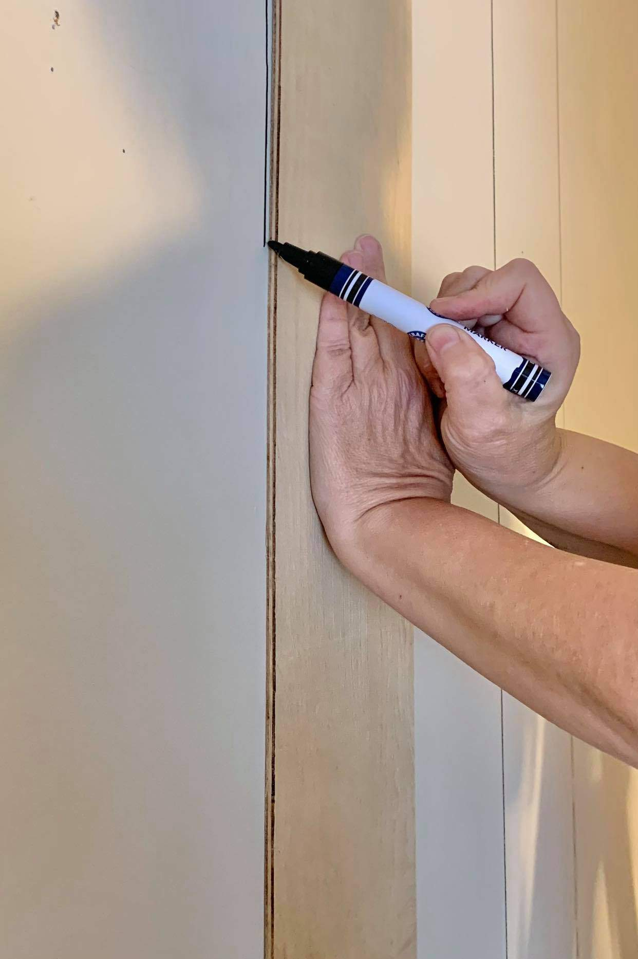 Use a Sharpie paint pen and draw a line down the wall.